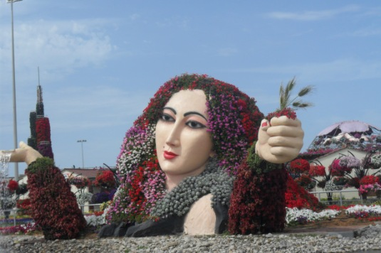 man made lake at the side of beautiful statue of women covered with flowers